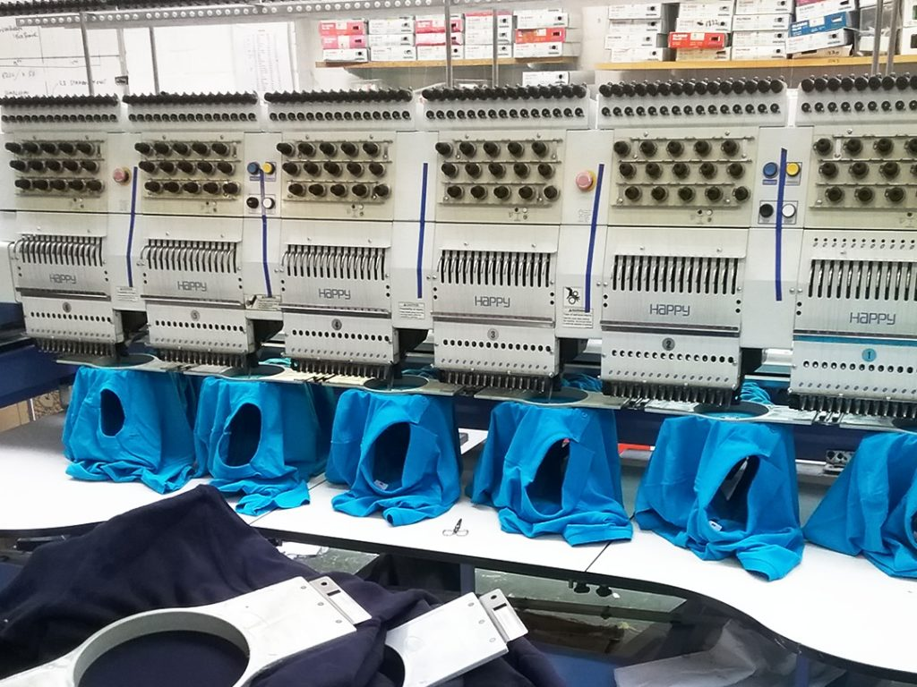 An image of a number of blue t-shirts being embroidered